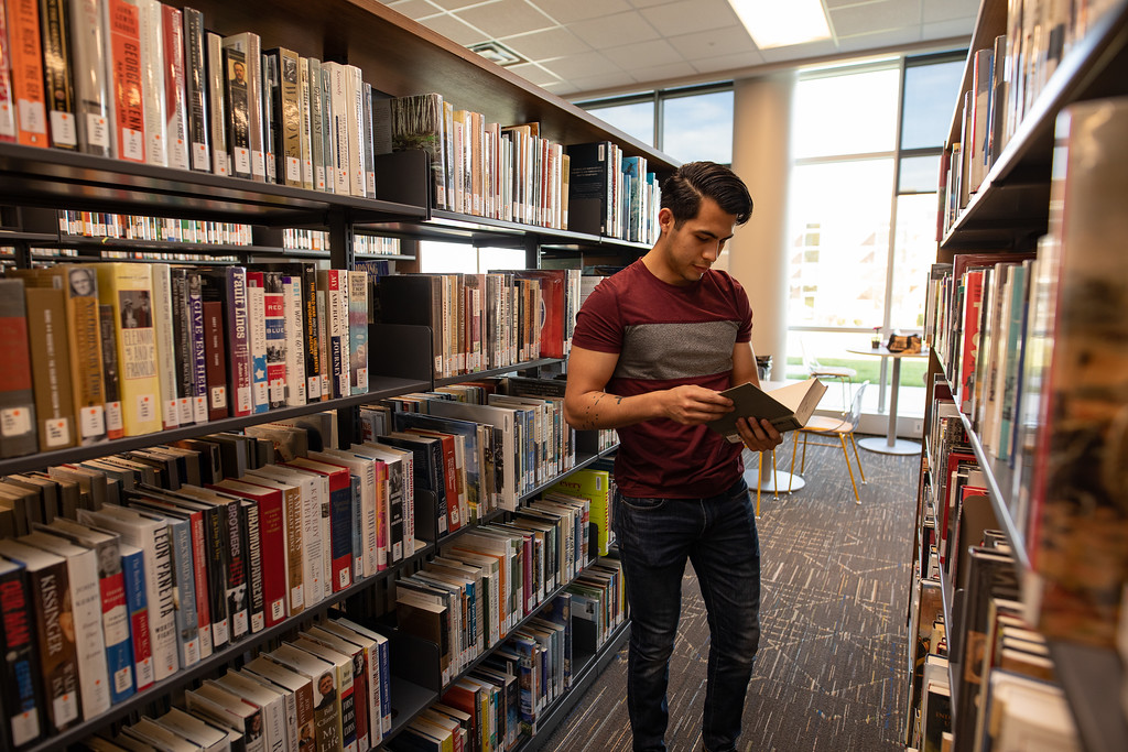 Student looking at book in the library