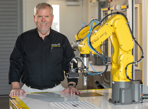 portrait of Charlie King with a FANUC robot