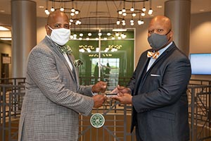 Dr Cary Holman shaking hands with Dr. Michael Torrence